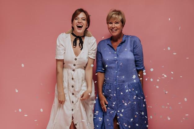 Ragazza con capelli castani in vestito bianco che ride e che posa con la donna bionda in vestiti blu su sfondo rosa isolato.