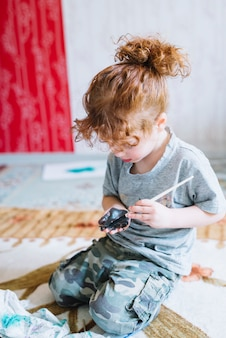 Girl with brush painting palm and sitting on floor