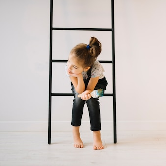 Girl with brush sitting on ladder near wall in room