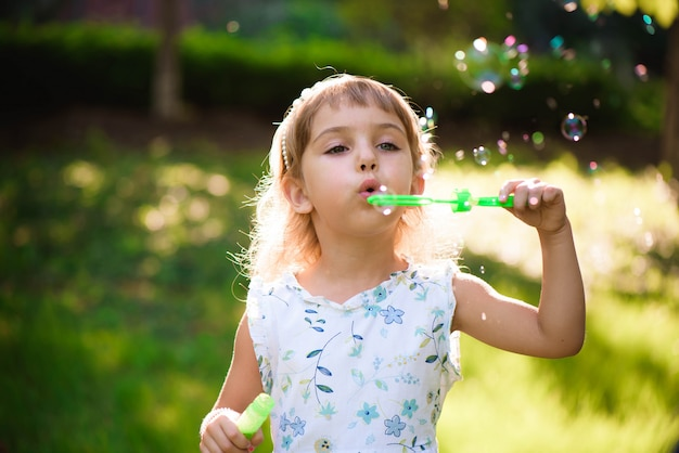 Girl with bubbles at a sunny summer evening