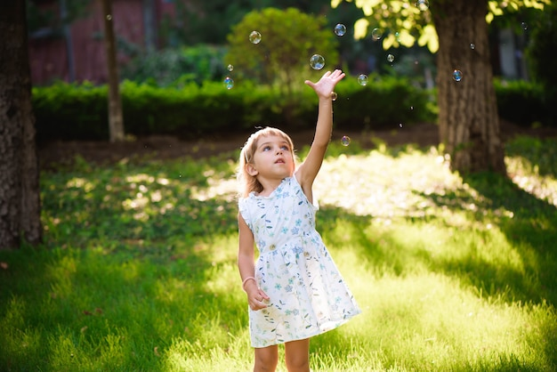 Girl with bubbles at a sunny summer evening.