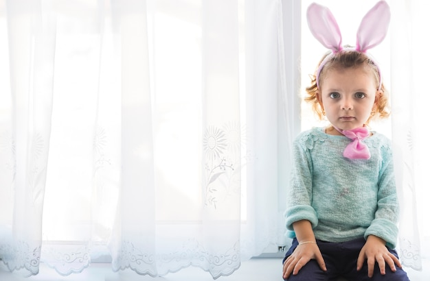 Girl with bunny ears looking at camera