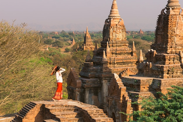 A girl with a burmese umbrella stands on top of the pagoda in bagan amid the setting sun and numerous pagodas.