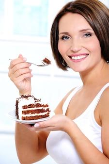 Девушка с тортом на тарелке подносит ложку ко рту