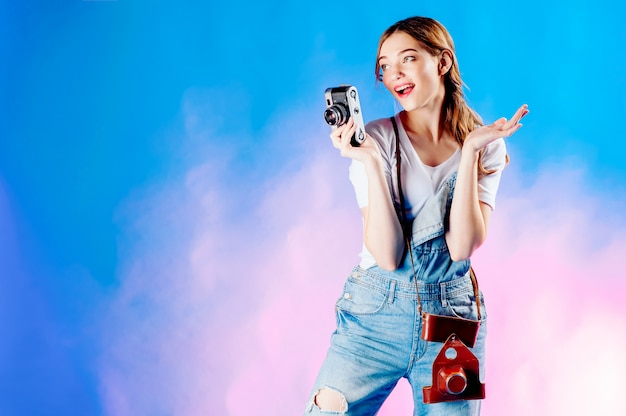 Girl  with a camera on a blue background going on vacation, tourism concept