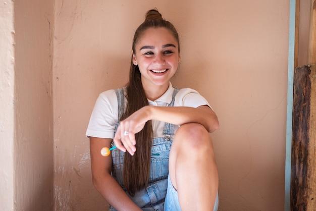 廃墟の家の棒にキャンディーを持つ少女。高品質の写真