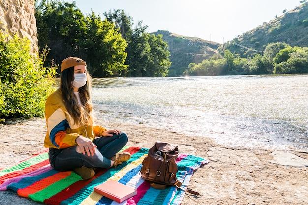 모자, 마스크, 황금 스포츠 재킷, 가죽 배낭 및 강가에 여러 가지 빛깔의 담요에 앉아 녹색 안경 소녀. 휴식 시간. 라이프 스타일 컨셉