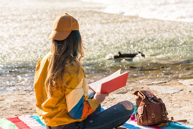 Girl with cap, sunglasses, golden sports jacket, leather backpack and green glasses sitting on a multicolored blanket by the river. reading a book in nature. relaxation time. lifestyle concept
