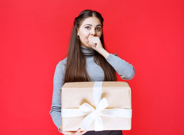Girl with a cardboard gift box looks terrified and tired.