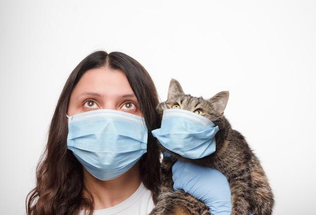 흰 벽에 보호 의료 마스크에 고양이와 여자. 코로나 바이러스 전염병 동안 동물을 돌보는 것. 2019 신종 코로나.