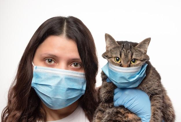 흰 벽에 보호 의료 마스크에 고양이와 여자. 코로나 바이러스 전염병 동안 동물을 돌보는 것. 사스 코로나 바이러스 2.