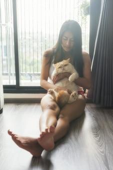 Девушка с кошкой спать возле окна