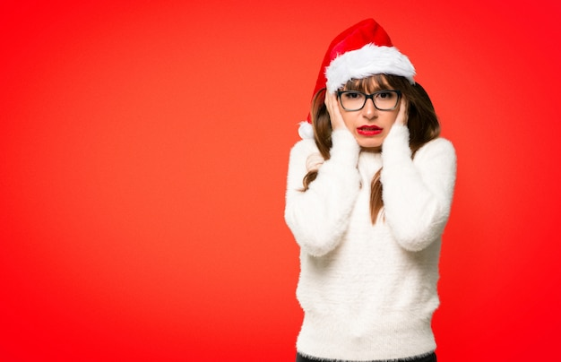 Girl with celebrating the christmas holidays covering ears with hands