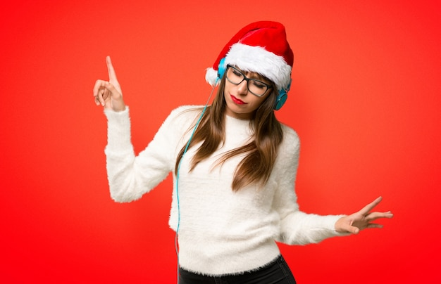 Girl with celebrating the christmas holidays listening to music with headphones and dancin
