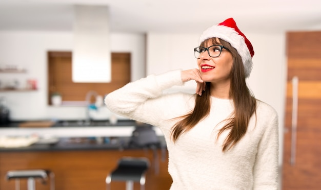 Girl with celebrating the christmas holidays making phone gesture. call me back sign at home