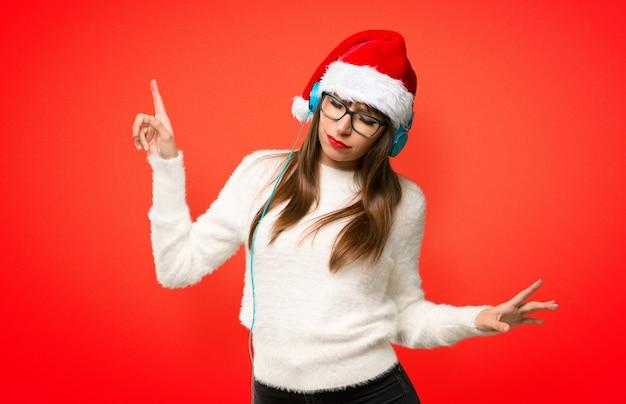 Девушка с празднованием рождественских каникул, слушая музыку с наушниками и dancin