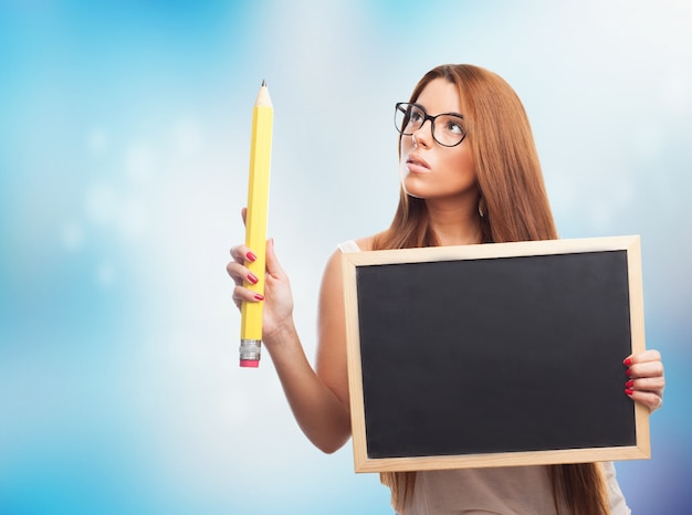 黒板や鉛筆を持つ少女