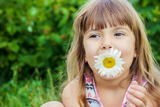 Girl with chamomile. selective focus. nature flowers.