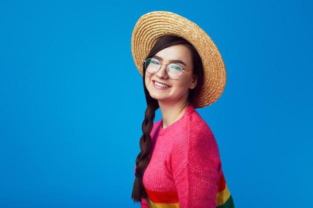 Девушка с веселым выражением лица в шляпе с радужным свитером и очках Premium Фотографии