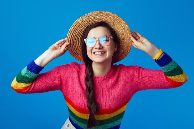 Девушка с веселым выражением лица в шляпе с радужным свитером и очках