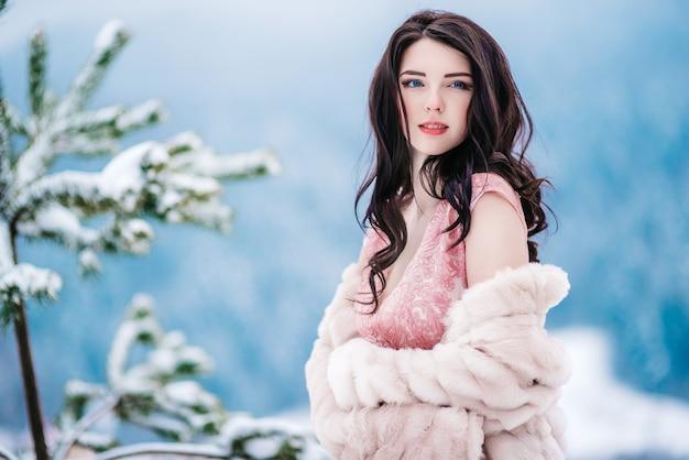 冬の山々を背景に栗色の髪、青い目、ピンクのドレスの女の子