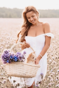 Girl with a chihuahua dog in a basket with a bouquet of flowers in nature in the summer field