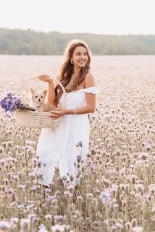 Girl with a chihuahua dog in a basket with a bouquet of flowers
