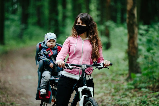 Girl with a child riding a bicycle in a medical mask on her face