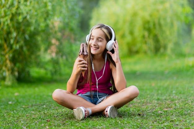 チョコレートアイスクリームとヘッドフォンを持つ少女