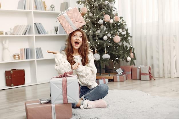 Девушка с рождественскими коробками. женщина дома. ладу готовится к праздникам.