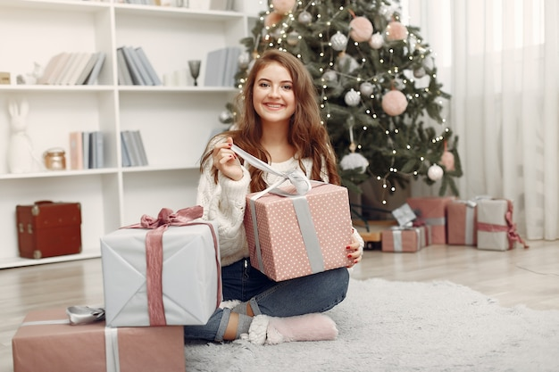 Girl with christmas boxes. woman at home. ladu preparing for holidays.