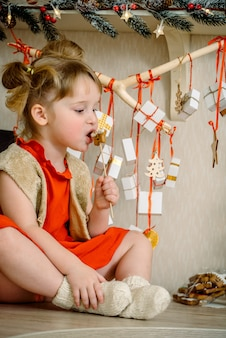 クリスマスのジンジャーブレッドと枝にぶら下がっている贈り物を持つ少女
