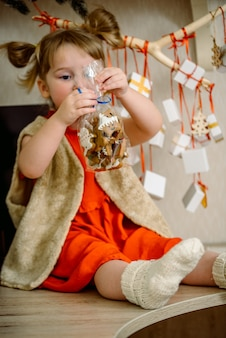 Girl with christmas gingerbread and gifts hanging on a branch