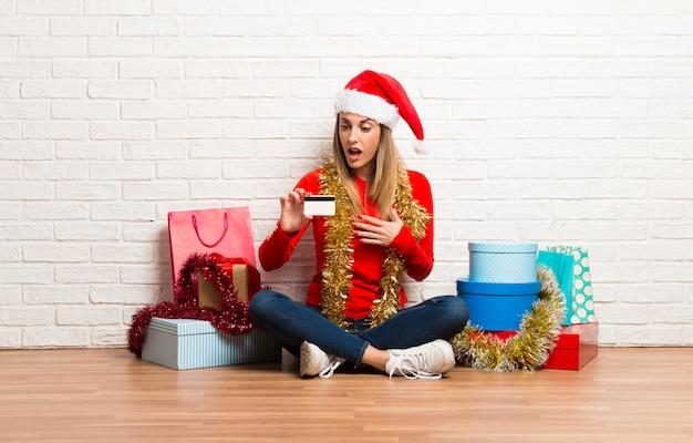 Девушка с рождественской шляпе и много подарков, празднующих рождественские праздники с кредитной картой