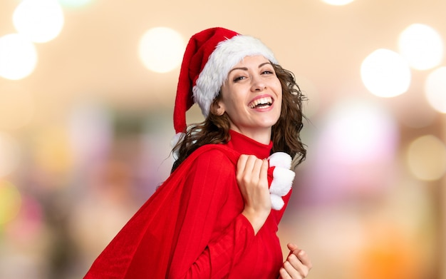 Girl with christmas hat holding a christmas bag full of gifts on unfocused background
