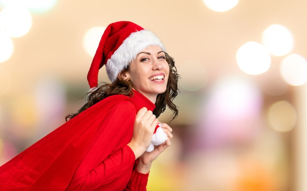 Girl with christmas hat holding a christmas bag full of gifts on unfocused wall