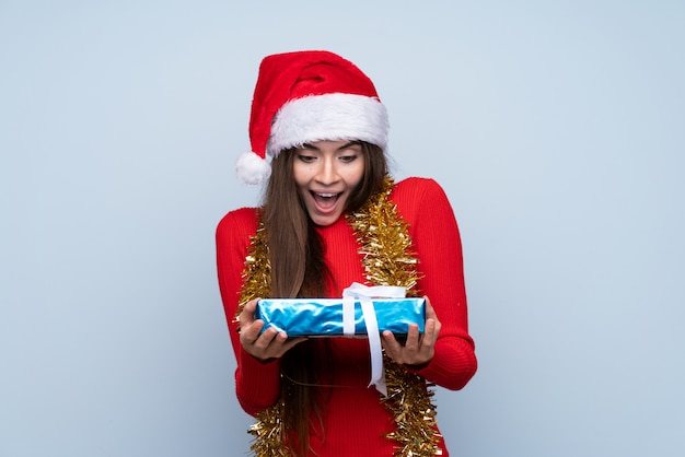 Girl with christmas hat and holding a gift over isolated blue