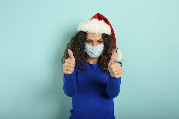 クリスマスの帽子をかぶった少女は、covid19コロナウイルスの敗北について楽観的です。