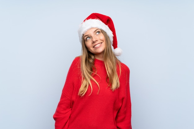 Girl with christmas hat over isolated blue wall laughing and looking up