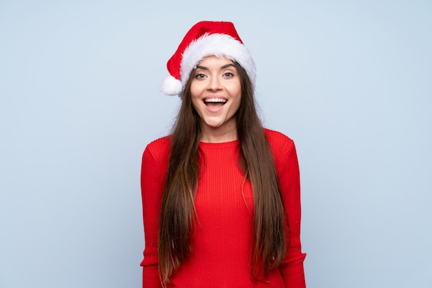 Girl with christmas hat over isolated blue with surprise facial expression