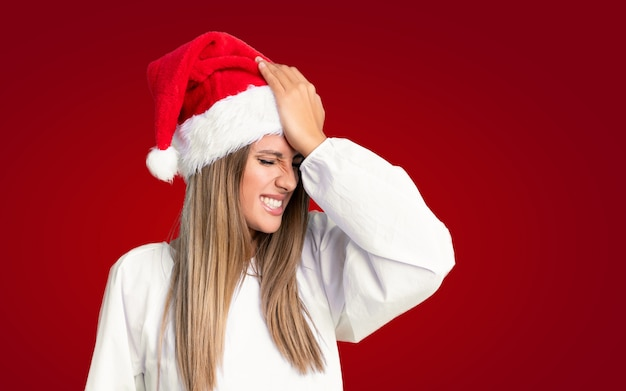 Girl with christmas hat over isolated wall having doubts with confuse face expression
