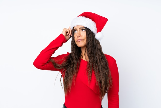 Girl with christmas hat over isolated white having doubts and with confuse face expression