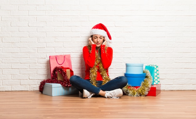 Girl with christmas hat and many gifts celebrating the christmas holidays covering both ea