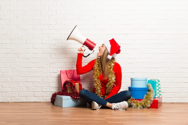 Girl with christmas hat and many gifts celebrating the christmas holidays holding a megaphone