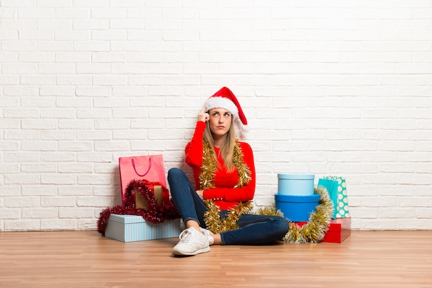 Girl with christmas hat and many gifts celebrating the christmas holidays standing and thi