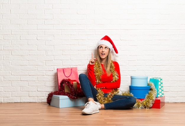 Girl with christmas hat and many gifts celebrating the christmas holidays standing