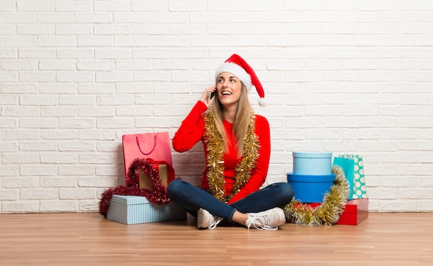Girl with christmas hat and many gifts celebrating the christmas holidays talking to mobile