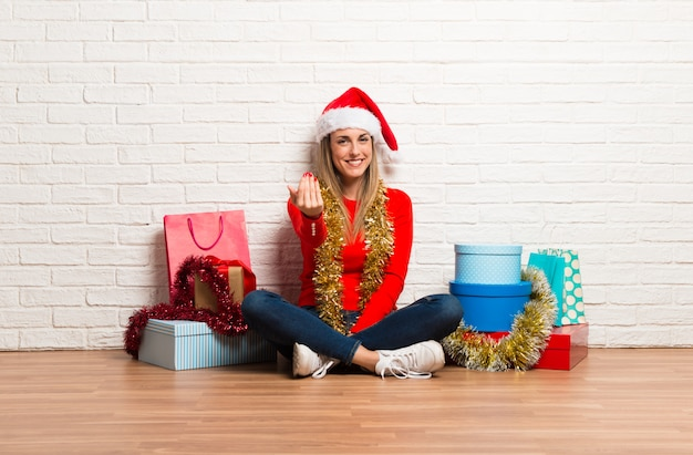 Girl with christmas hat and many gifts celebrating the christmas holidays