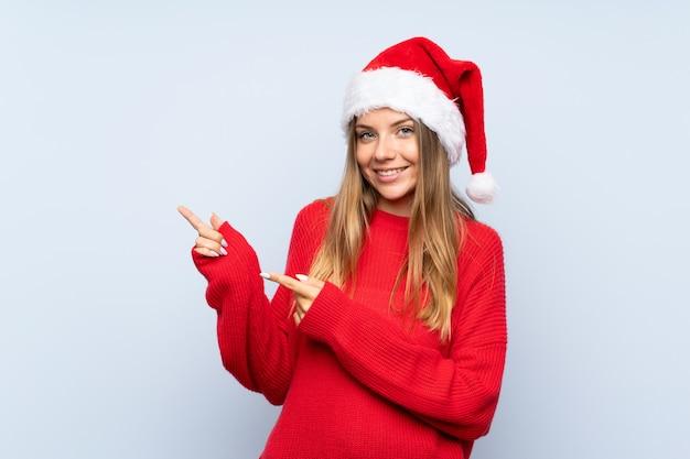 Девушка с шляпой рождества над изолированной голубой стеной указывая палец в сторону