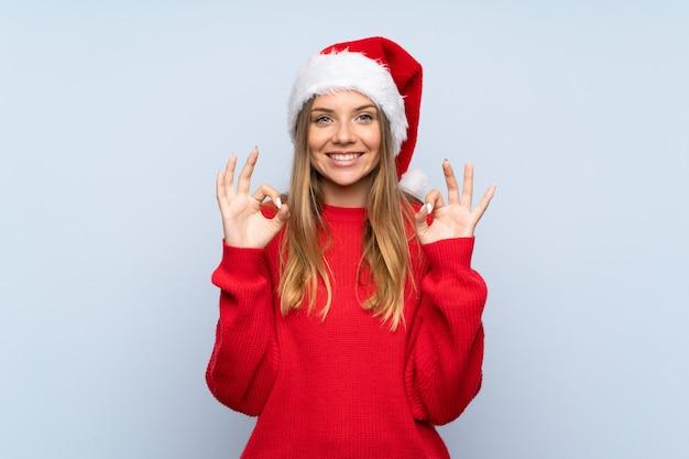 Девушка с шляпой рождества над изолированной голубой стеной показывая одобренный знак с пальцами